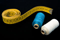 Measure tape and  thread bobins. Measure tape and a couple of thread bobbins on black background Royalty Free Stock Photo
