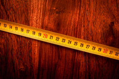 Measure tape on wood. Yellow measure tape on solid wood Royalty Free Stock Images