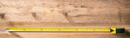 Measure tape on wooden background, banner, copy space, top view Stock Image