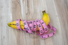 Measure tape wrapped around  banana on wood table . Royalty Free Stock Photos