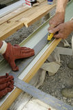 Measure Twice and Cut Once. Two pair of workers' hands measuring and cutting vinyl siding Royalty Free Stock Image
