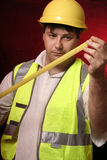 Measure up. Builder with his trusty tape measure on a black/red background Royalty Free Stock Image