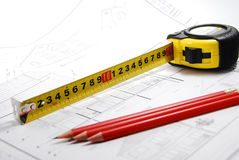 Measure up. Measure and pencils over technical plans Stock Images