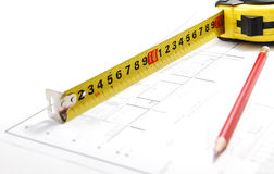 Measure up. Tape measure over architectural plans and red pencil Stock Photography