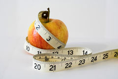 Measured apple. An apple with measuring tape wrapped around it Stock Photo