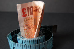 Measured Cost 2. This is an image of a ten pound note and measuring tape. (Please let me know where the image will be used by leaving a message in the Comments royalty free stock photos