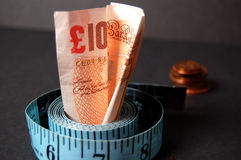 Measured Cost. This is an image of a ten pound note and few pennies in the background. (Please let me know where the image will be used by leaving a message in stock image