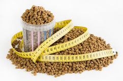Measured dose of food for dog. Measuring cup for dog dry food with measuring tape for recommended dose stock photo