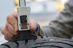 Measured tread. Mechanic measures with profiler for winter tires, the tread depth Royalty Free Stock Photo