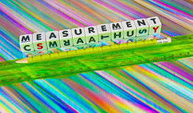 Measurement. Text ' measurement ' inscribed in black uppercase letters on small white cubes beside green ruler and green pencil, multicolored background stock photo