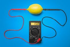 Measurement of electric tension in lemon. Blue background.  stock photo