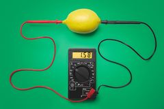 Measurement of electric tension in lemon. Green background.  royalty free stock photo