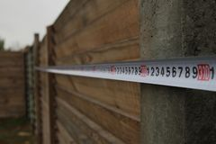 Measurement of a fence with a construction tape measure in the suburban area Royalty Free Stock Image