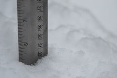 Measurement of Fluffy White Snow. A silver ruler is used to measure accumulation of white fluffy snow royalty free stock images