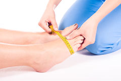 Measurement of foot. Young physiotherapist measures the foot Stock Photos
