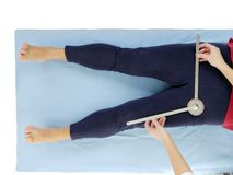 Measurement of hip joint abduction. Physiotherapist measuring active range of motion of older patient's lower limb using manual goniometer Stock Photography