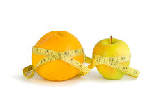 Measurement of orange and apple Royalty Free Stock Photos