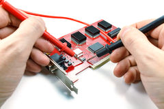 Measurement of parameters on the DVR motherboard with a multimeter on a white background Royalty Free Stock Photo