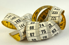 Measurement tape. An old used yellow and white measurement in centimeters and millimeters on grayish background stock photo