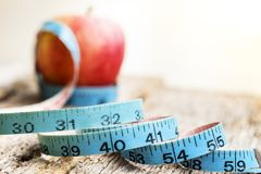 Measurement tape with red apple in background Stock Photos