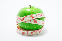 Measurement tape wrapped around green apple. Isolated against white background royalty free stock images