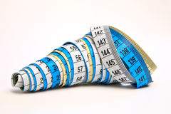 Measurement tapes swirled together. Three measurement tapes, white, blue and yellow, swirled together Royalty Free Stock Photography