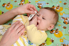 Measurement of temperature to the sick crying baby the electronic thermometer.  stock photography