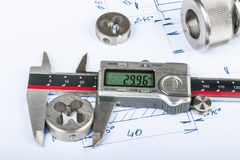 Measurement of thread cutting die by calipers and technical drawing. Metal engineering parts and the digital measuring tool placed on the manufacturing Stock Images