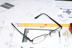 Measurement tool and glasses over blueprints Stock Image