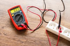 Measurement voltage in electrical socket with multimeter stock image