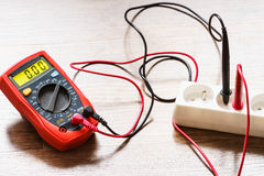 Measurement voltage in electrical socket with multimeter. Measurement of voltage in electrical socket extension cord with multimeter on wooden floor background stock photo