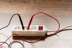 Measurement voltage in electrical socket with multimeter royalty free stock photo