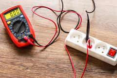 Measurement voltage in electrical socket with multimeter royalty free stock images