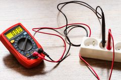 Measurement voltage in electrical socket with multimeter stock photos