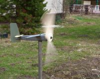 Fast rotating blades of weather vane in garden. Measurement of wind speed. Strong wind stock photography