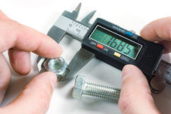 Measurements by a digital caliper in the master`s hand stock photography