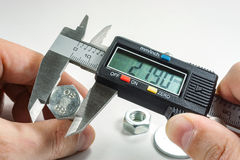 Measurements by a digital caliper in the master`s hand stock photo