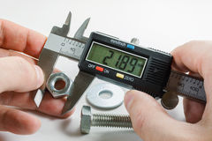 Measurements by a digital caliper in the master`s hand stock images