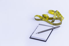 Measures. Notepad and tape measure. White background Royalty Free Stock Photography