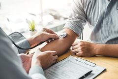 Measuring医生与人患者的动脉血压力胳膊医疗保健的在医院 免版税库存图片