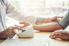 Measuring医生动脉血压力胳膊医疗保健的人患者在医院 免版税库存图片