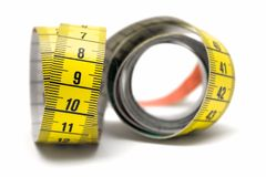Measuring. Winding tape measure against white Royalty Free Stock Photos