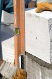 Measuring. A worker measuring some bricks Stock Photos