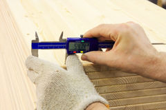 Measuring. Closeup shot of workers hands measuring wooden item Royalty Free Stock Photos