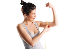 Measuring. Young and sexy blond woman smile, measuring her arm muscle by measure tape, isolated over white background Stock Photos