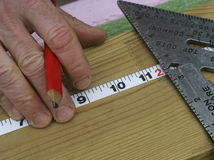 Measuring. Close view of hand with pencil and tape measure, measuring a piece of lumber Royalty Free Stock Photo