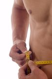 Measuring. Young pretty man measuring his perfect body isolated on white Stock Photography