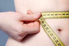 Measuring. Young woman measures her belly Stock Photo