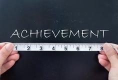 Measuring achievement. Tape measure aligned against achievement Royalty Free Stock Image