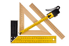 Measuring the angle and length. Metallic tool to measure right angle, triangle and wooden ruler, pencil and tape measure on a white background Royalty Free Stock Photography